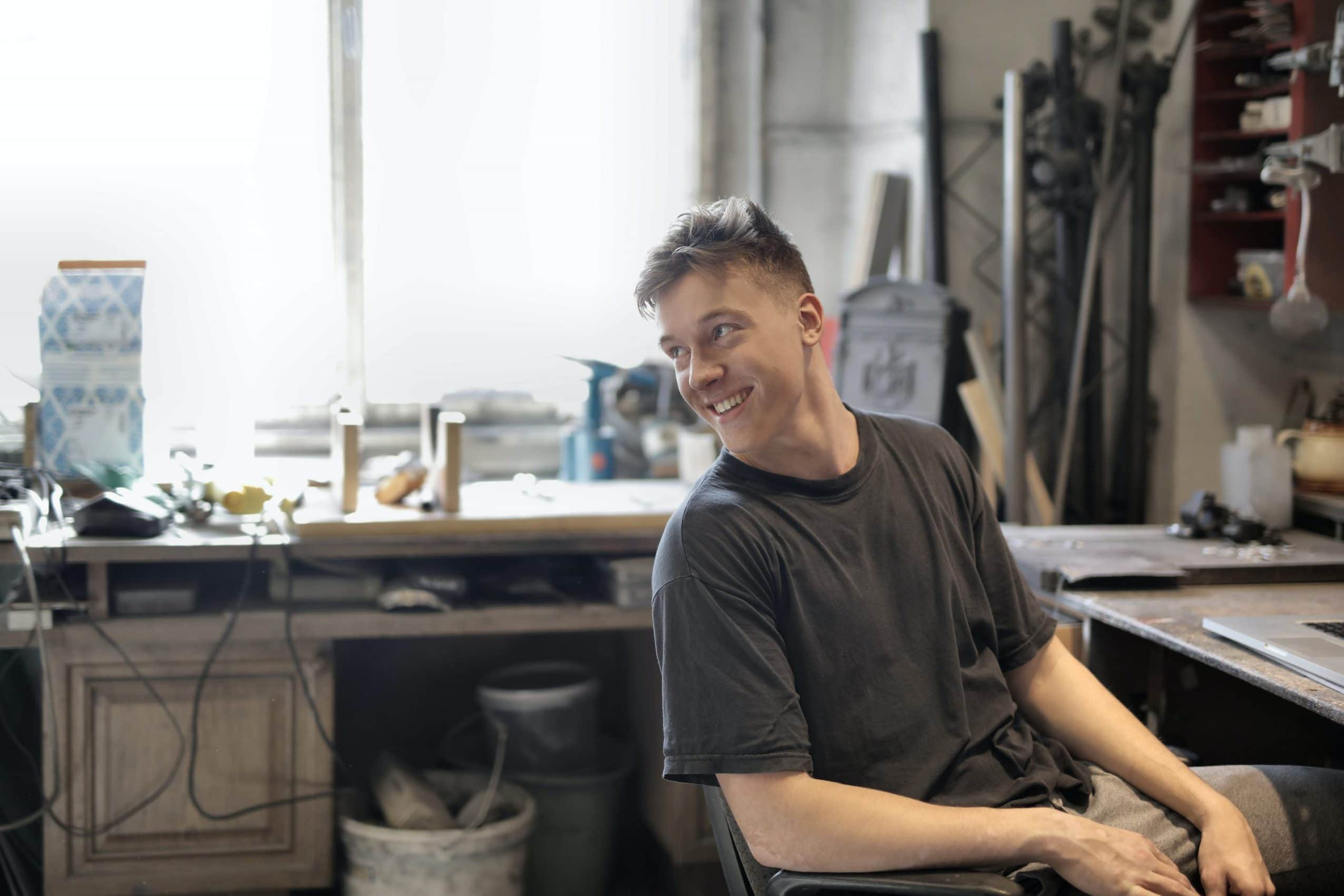 cheerful-man-sitting-at-table-in-workshop-3844524