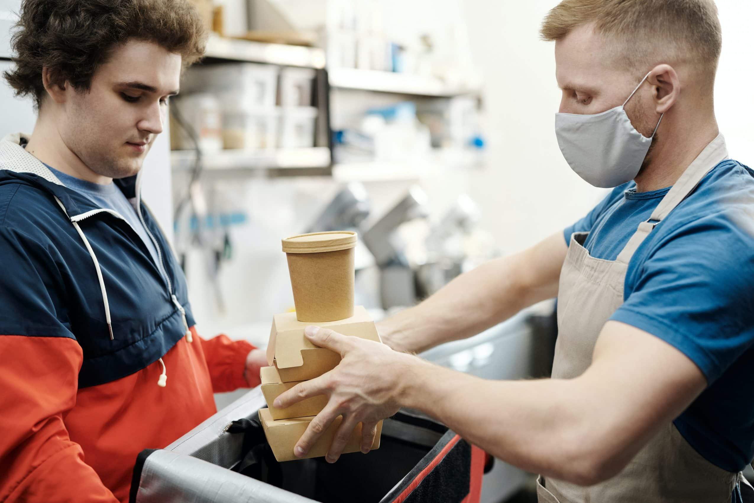 men-putting-food-on-a-thermal-bag-4393665