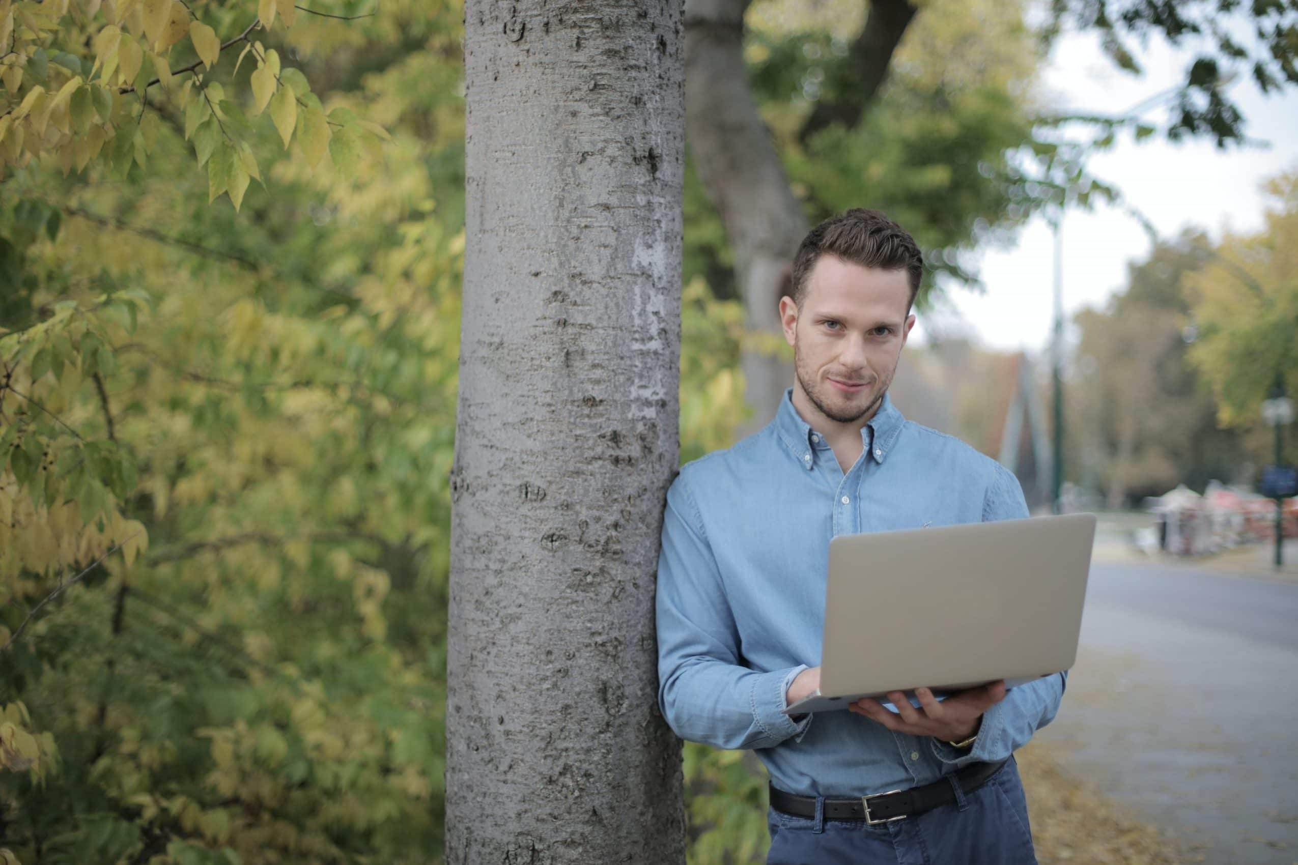 positive-young-man-using-laptop-near-tree-in-park-3973338