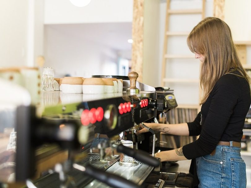 A Young Female Barista Making Coffee