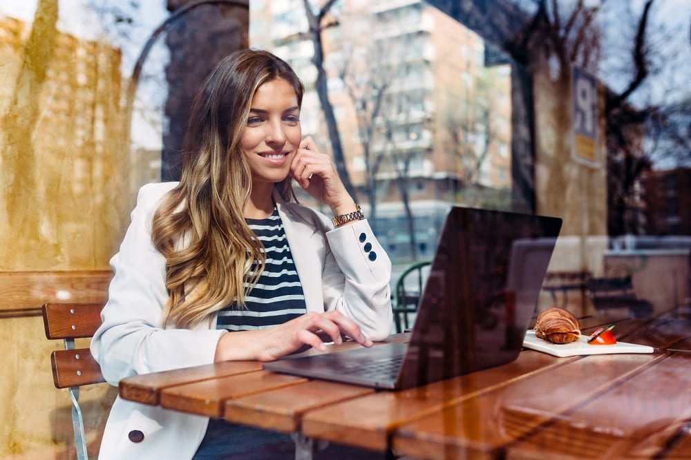 Happy Businesswoman Using Laptop In Cafeteria