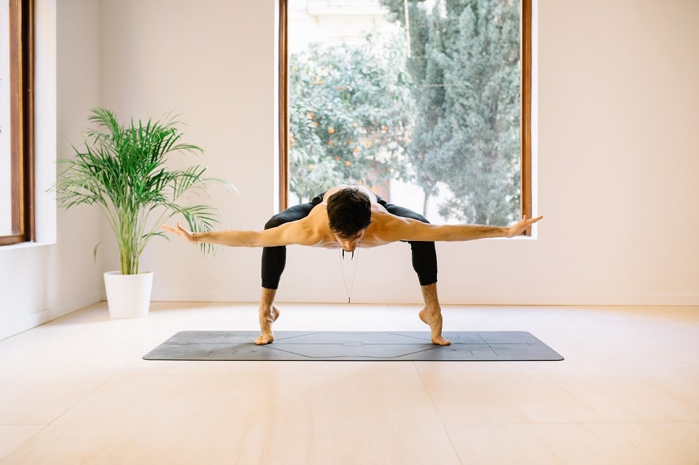 Shirtless Yogi Stretching On Mat