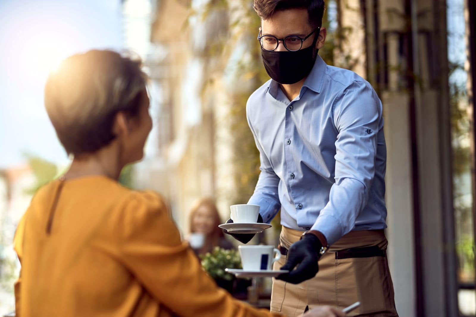 Young,Waiter,Wearing,Protective,Face,Mask,While,Serving,Coffee,To